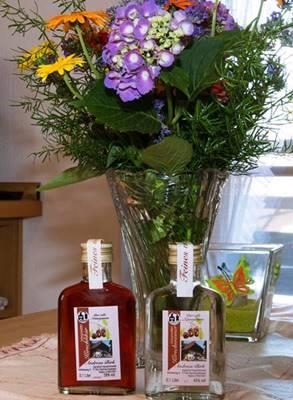 Blumenstrauß und Probierfläschchen mit Kirschlikör und Kirschwasser auf dem Küchentisch
